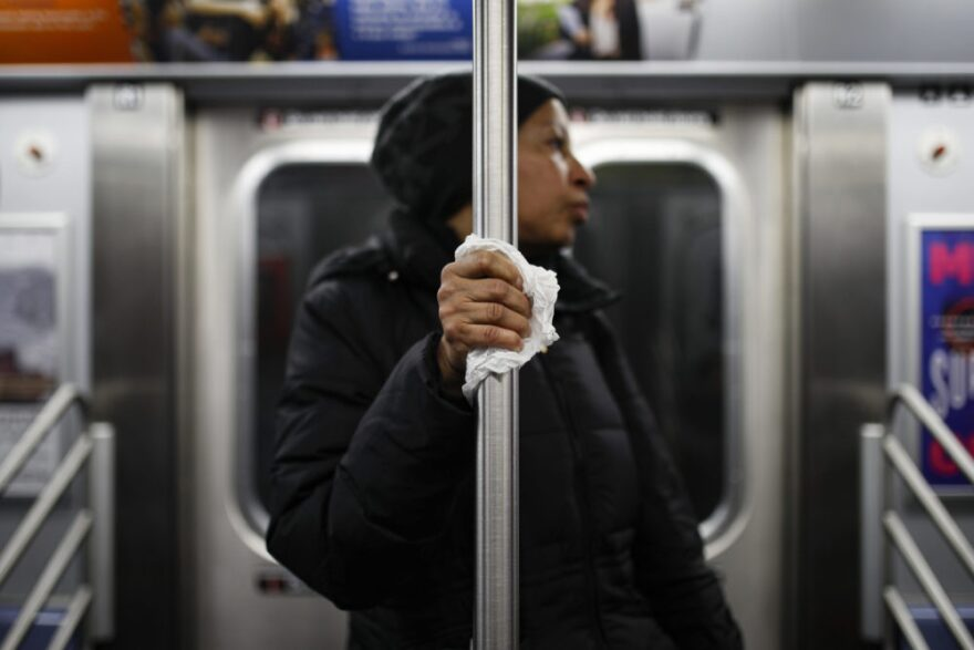 A subway customer uses a tissue to protect her hand while holding onto a pole as COVID-19 concerns drive down ridership, Thursday, March 19, 2020, in New York. (John Minchillo/AP Photo)