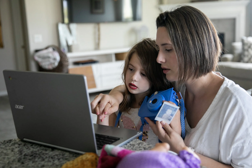Five-year-old Nora gets a hand from her mother, Melissa, as she meets with her new kindergarten class virtually in the family's home in Katy.