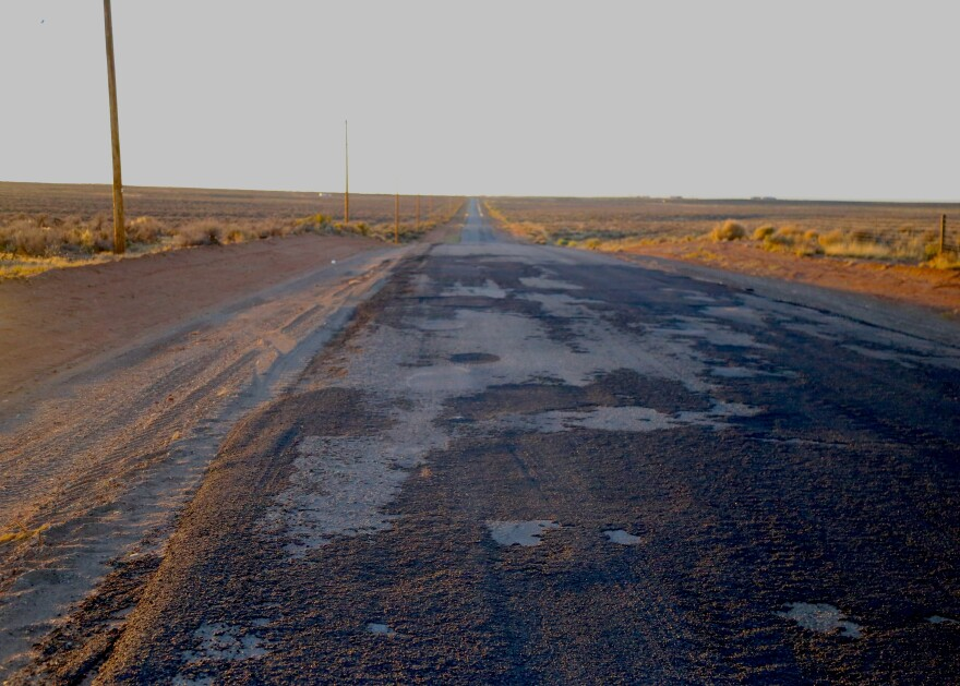 A road with worn pavement and lots of patches.