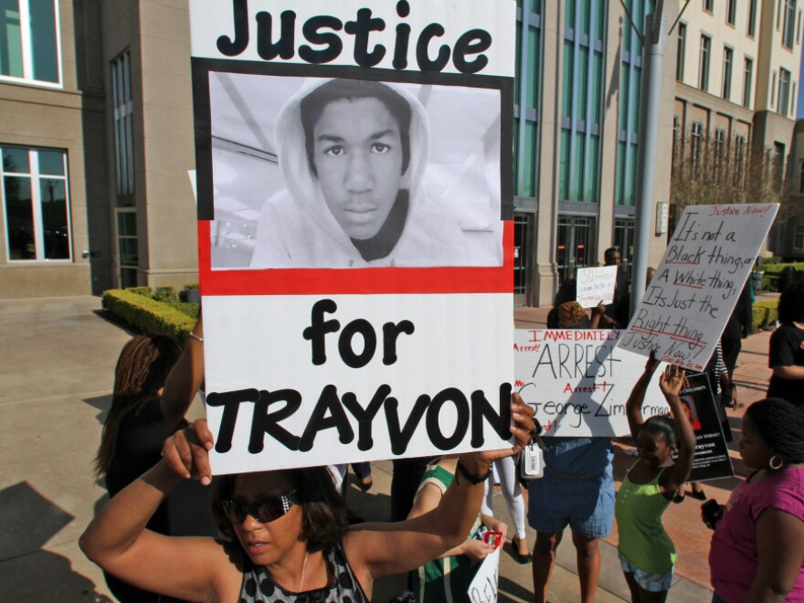 Demonstrators rally at the Seminole County Courthouse on Monday, demanding the arrest of a neighborhood watch captain who shot Martin, an unarmed black teen, last month.