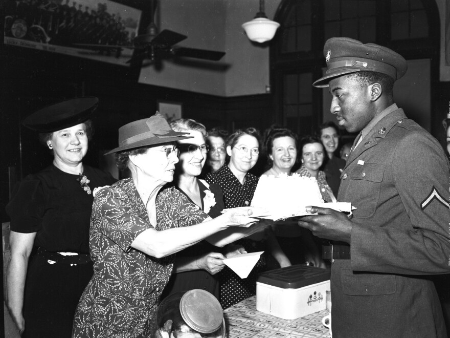 Army PFC Clifton Hall accepts a cake from volunteer Lyda Swenson.