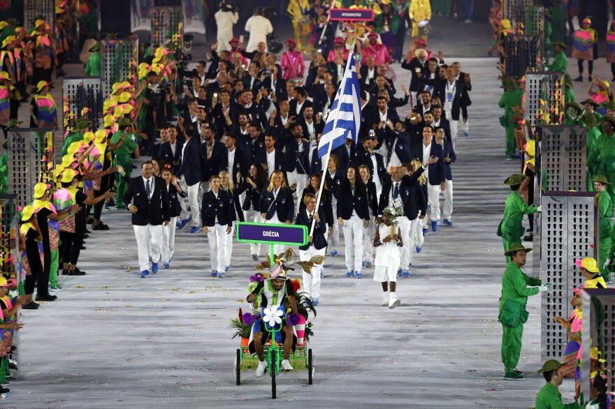 Athletes come out led by a tricked-out florescent three-wheeled bicycle. As is customary at the Olympics, the first delegation out of the gate is that of Greece.