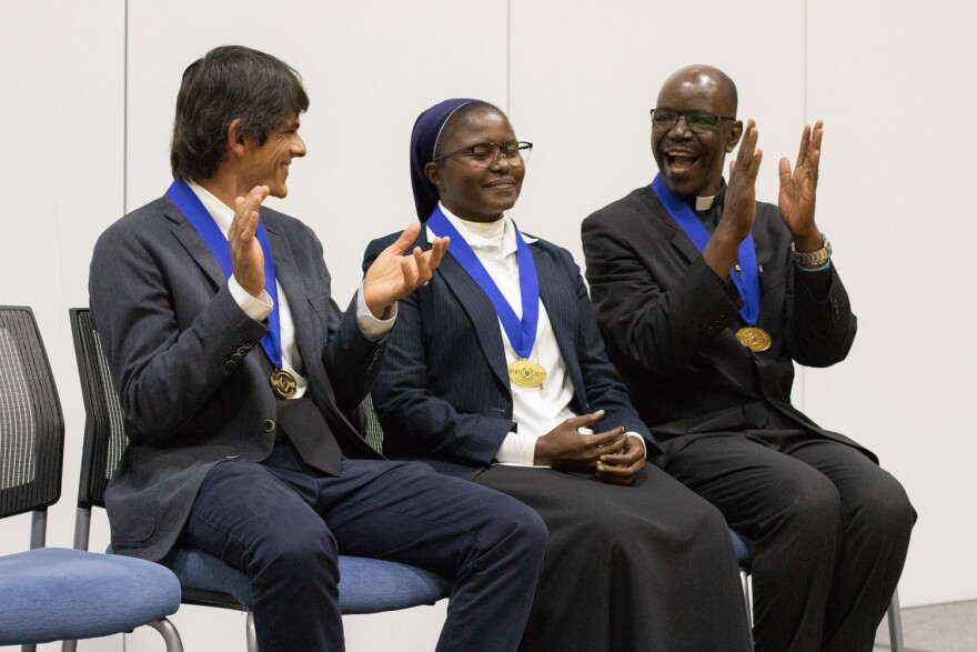 Sister Catherine Mutindi (center) reacts to being named the 2019 Opus Prize winner while finalists Michael Fernandez-Frey (left) and Brother Charles Nuwagaba (right) applaud.  11/21/19