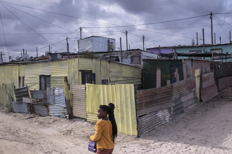 A girl walks past shacks in the township of Khayelitsha, Cape Town, South Africa. There are fears that it will be hard to control the spread of the coronavirus if it takes hold in the densely populated township, where dozens of people share a single communal toilet and families often share a single room.