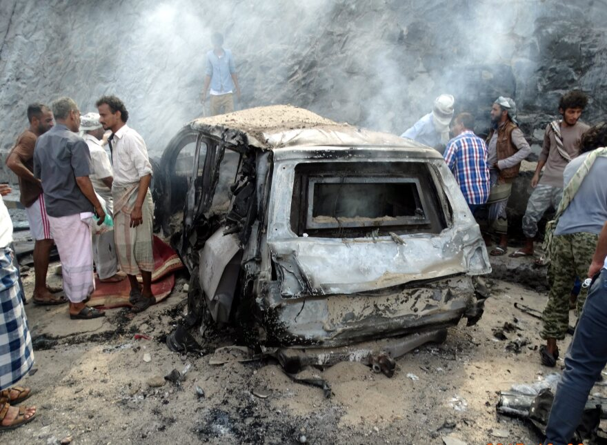 Yemenis inspect the scene of a car bomb attack that killed a Yemeni senior official in the southern port city of Aden, Yemen, on Sunday.