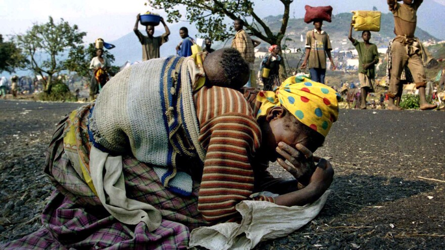 A Rwandan woman collapses with her baby on her back on the road near Goma, Zaire, in 1994. Many Rwandans fled across the border into what was then Zaire, now known as the Democratic Republic of Congo.