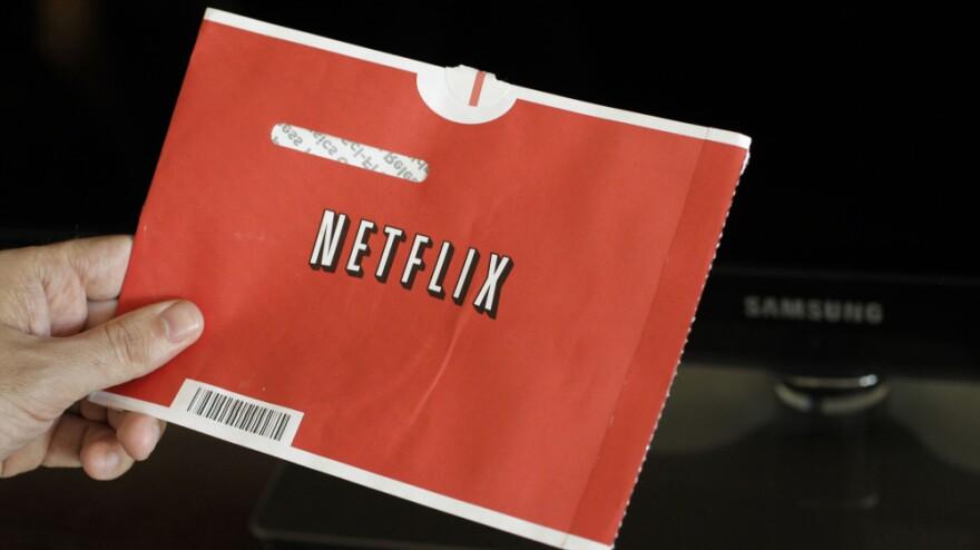 A Netflix customer holds up a movie envelope.