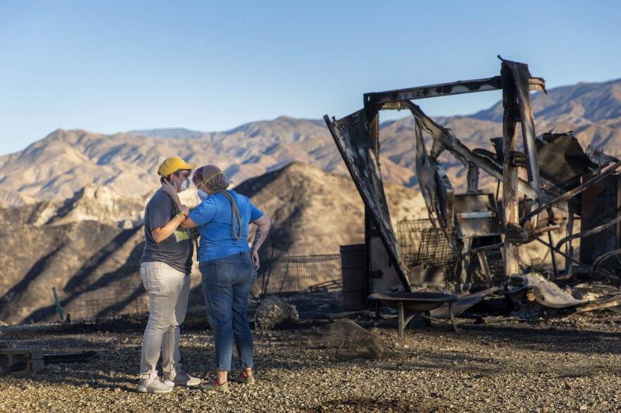 Lanthier and Hull pause for a moment while picking up some of their livestock that didn't make it out of the fire on Thursday. The two, who had about 80 animals, were able to rescue only 20 because of the fast-moving flames.