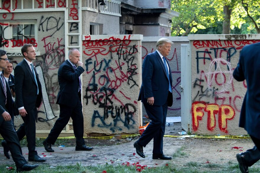 After the police's use of tear gas to clear the area, President Trump emerges from the White House and gets escorted through Lafayette Square to St. John's Episcopal Church for a photo on June 1.