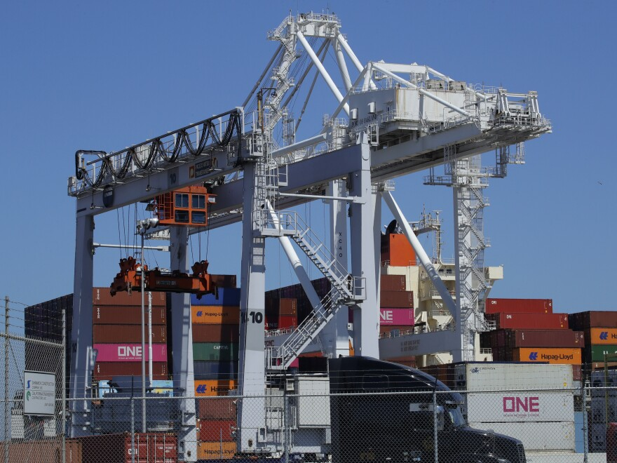 A container ship is unloaded at the Port of Oakland in California. A drop in exports contributed to a slowdown in U.S. economic growth in the second quarter.