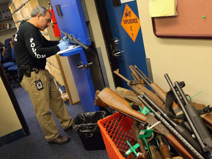 Detective Enrique Chavez logs weapons from a gun buyback in Miami. Arizona's new law requires municipalities to re-sell weapons recovered in such programs.
