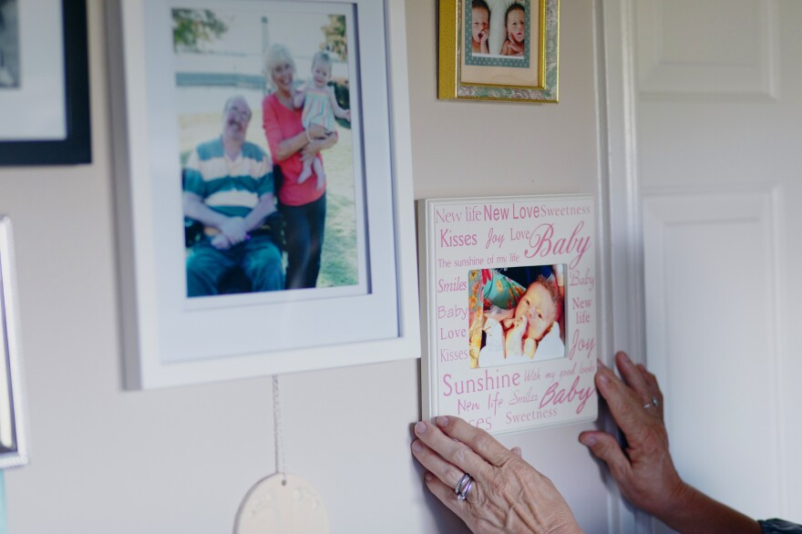 Luann Thibodeau adjusts a family photo in her home. Before the coronavirus outbreak, she would take her husband to church on Sunday and to the movies. They'd go out for fast food. But she says his anxiety has increased since the lockdown began.