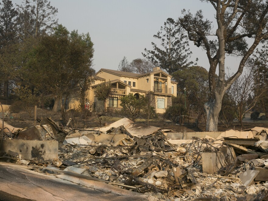 A large home that survived last week's wildfire sits by the burned ruins of one that did not, on Monday in Santa Rosa, Calif.
