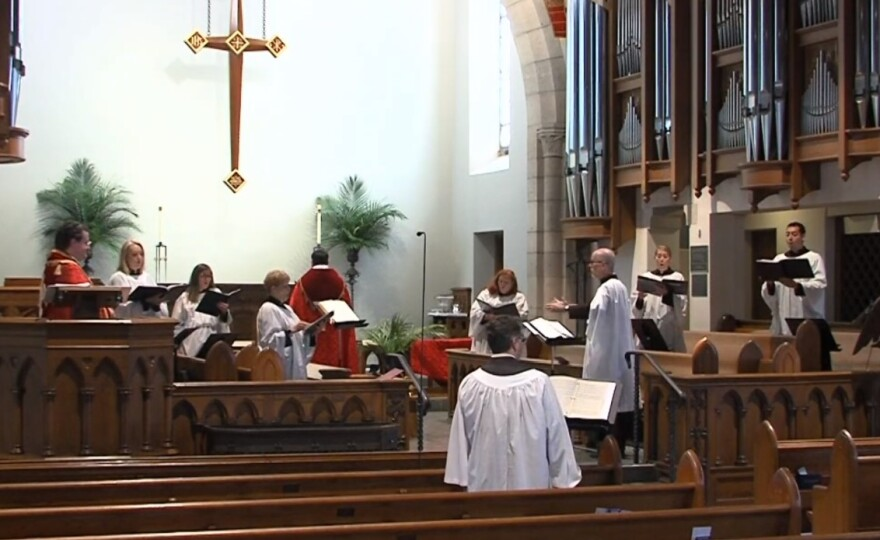 A shot of inside a church with people in white robes singing