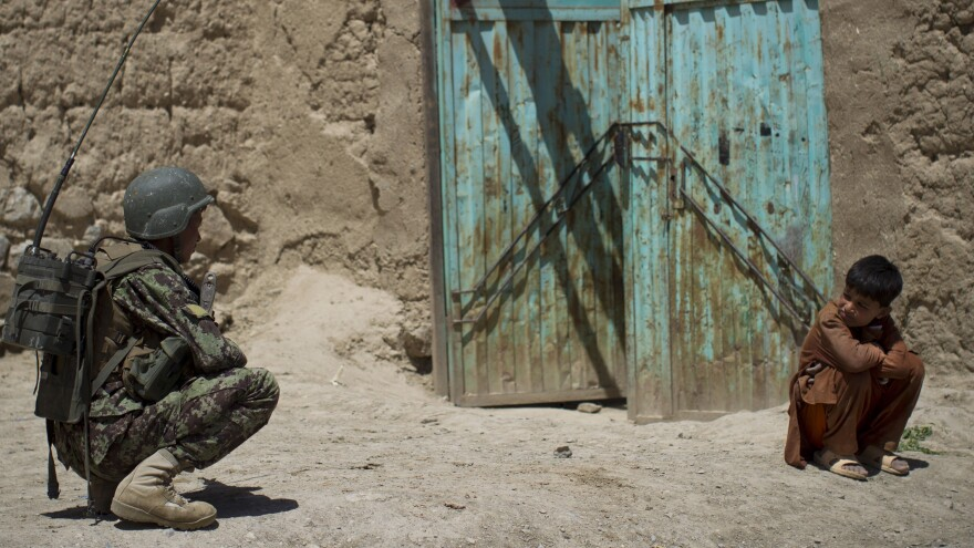 An Afghan boy watches an Afghan National Army soldier on patrol in Logar province, eastern Afghanistan, on May 17. NATO forces are scheduled to leave Afgahnistan by the end of 2014.