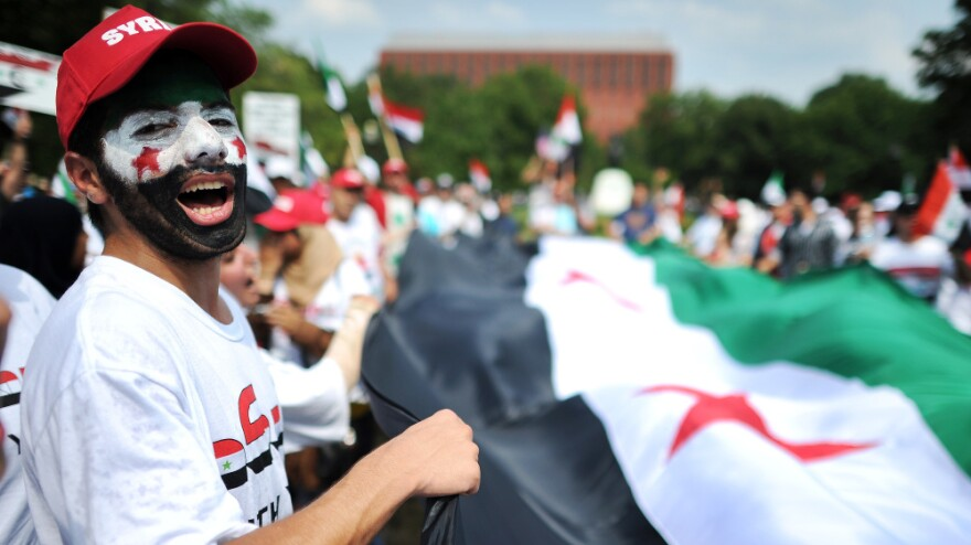 <p>Protesters shout slogans against the Syrian government in front of the White House in July. A new report from Amnesty International documents more than 30 cases of Syrian activists living overseas whose activities have been monitored and whose families in Syria have been threatened.</p>