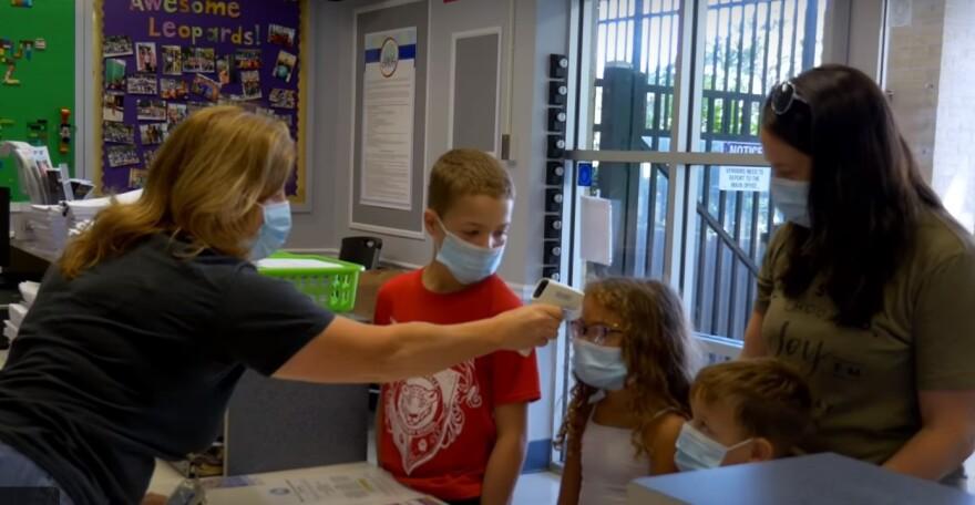 A screenshot of children getting their temperature taken at school