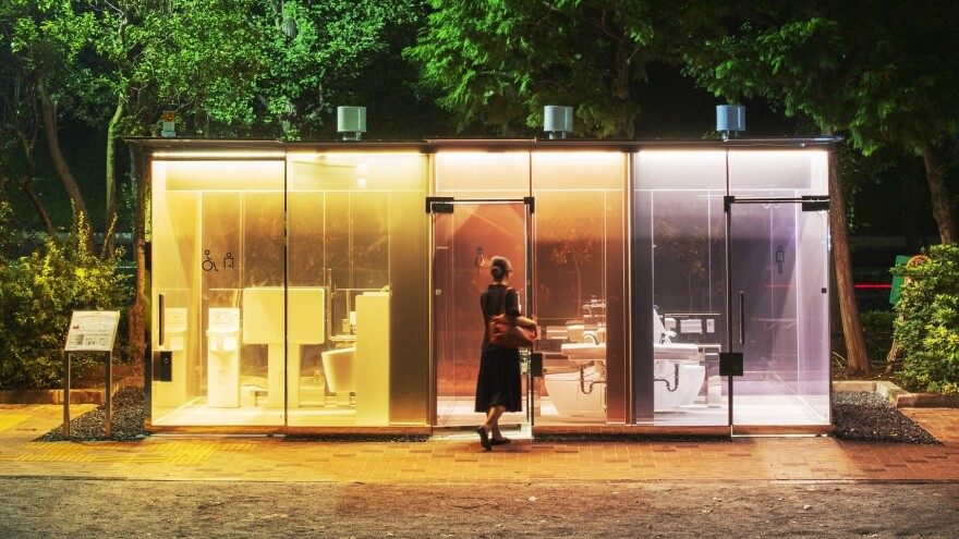 A woman enters a public restroom with transparent walls in Tokyo's Shibuya ward. Architect Shigeru Ban designed the bathroom in a way to reassure anyone entering the toilet.