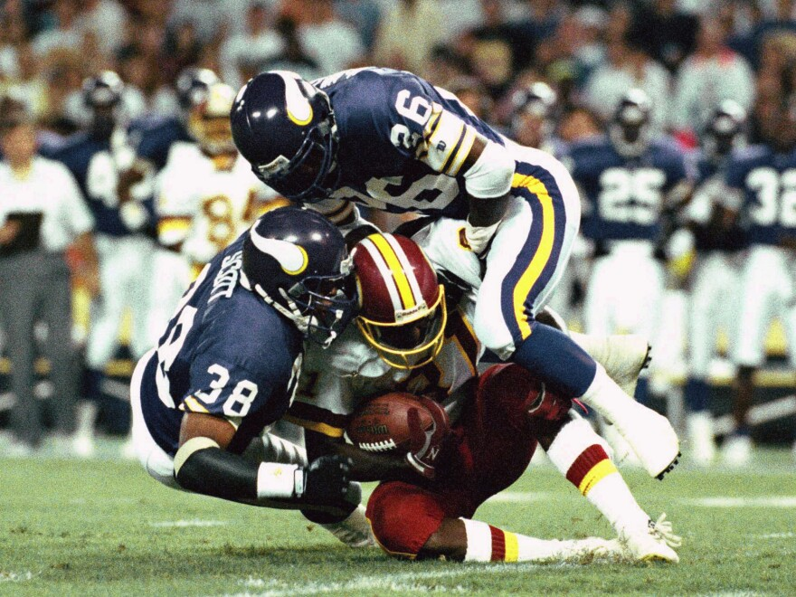 Minnesota Vikings players bring down Washington wide receiver Art Monk during an NFL game in 1992. Monk was one of the lead plaintiffs in the $1 billion settlement with the NFL over brain injuries among former players.