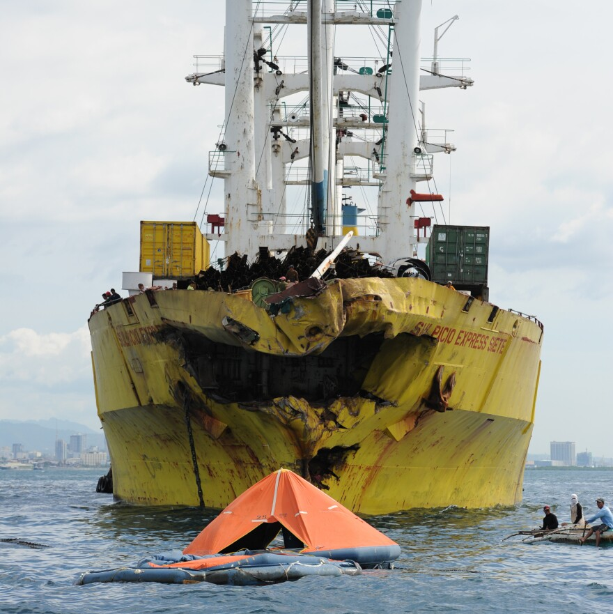 A life raft from the sunken ferry MV Thomas Aquinas floats in front of the cargo ship it collided with on Friday.