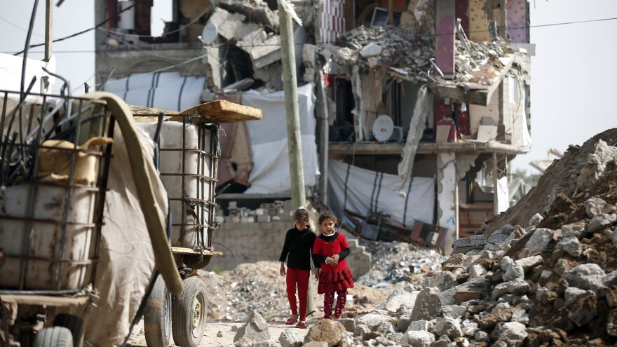 Palestinian girls walk past buildings in Gaza City that were destroyed during the 50-day war between Israel and Hamas militants in the summer of 2014. Dozens of Israeli soldiers have now given testimonials saying that indiscriminate firing was tolerated, or even encouraged at times.