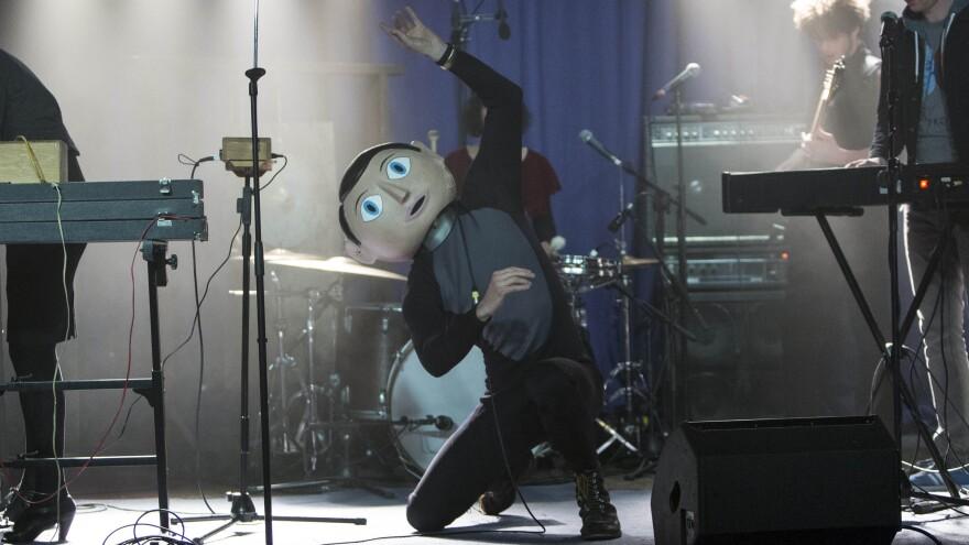 Michael Fassbender stars as Frank, the mysterious papier-mache head-wearing lead musician of an offbeat pop band called Soronprfbs in Lenny Abrahamson's <em>Frank</em>.