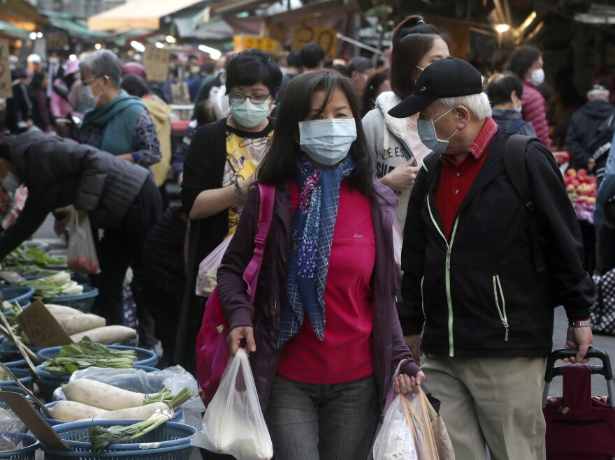 People wear face masks to help curb the spread of the coronavirus as they shop at a market in Taipei in April.