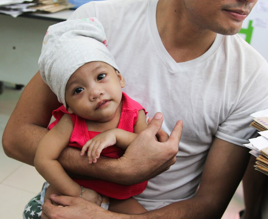 At the Corazon Aquino Health Center in Manila, a father holds a piece of gauze against his son's arm. The 14-month-old had just been given an injection to immunize him against measles and rubella.