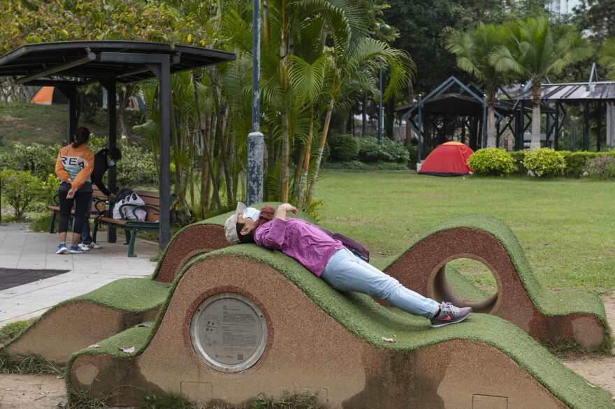 New rules in Hong Kong require everyone to wear a mask in all outdoor places or face a $650 fine. Above: A masked woman stretches out a public park. Also: The maximum number of people allowed at a public gathering is ... 2.