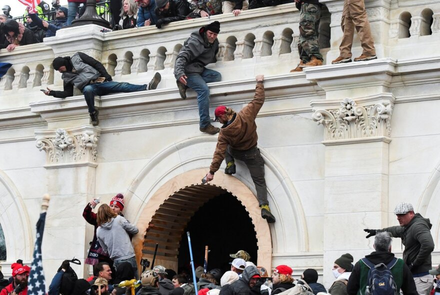 Rioters scaling the walls at the U.S. Capitol.