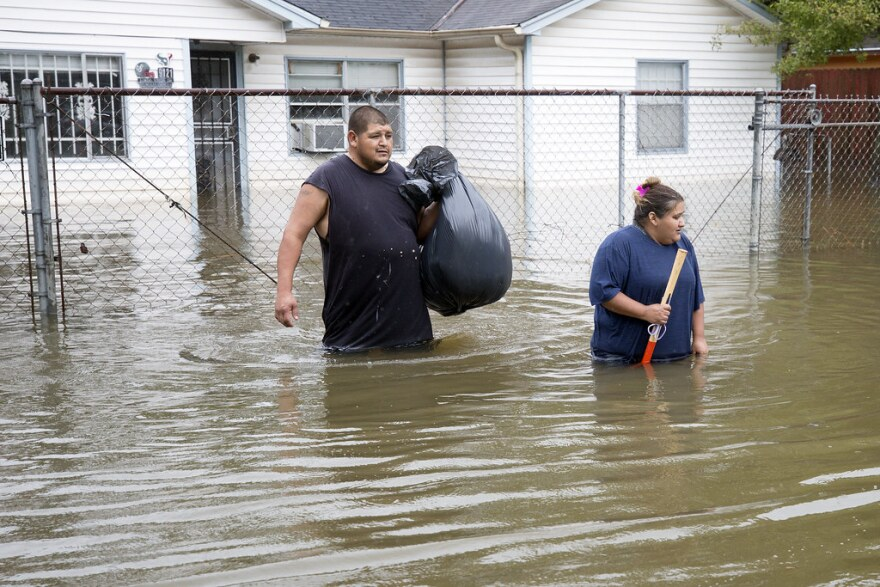 Raul and Christy Garcia wade through water in East Houston.
