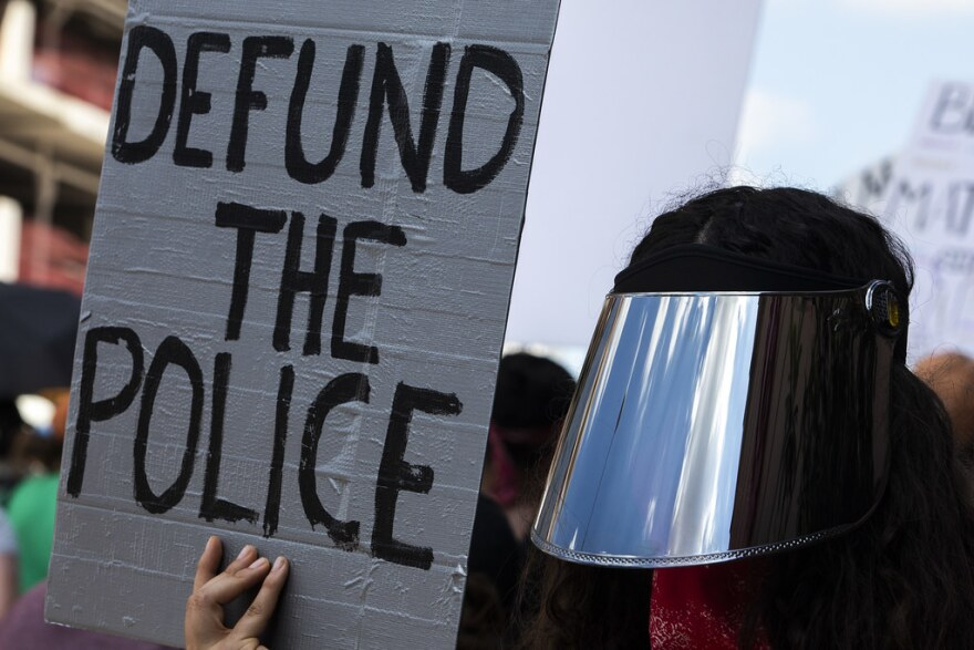 A protestor holds a sign calling for police defunding as thousands march from the Texas State Capitol to Huston-Tillotson University as part of the March for Black Lives.
