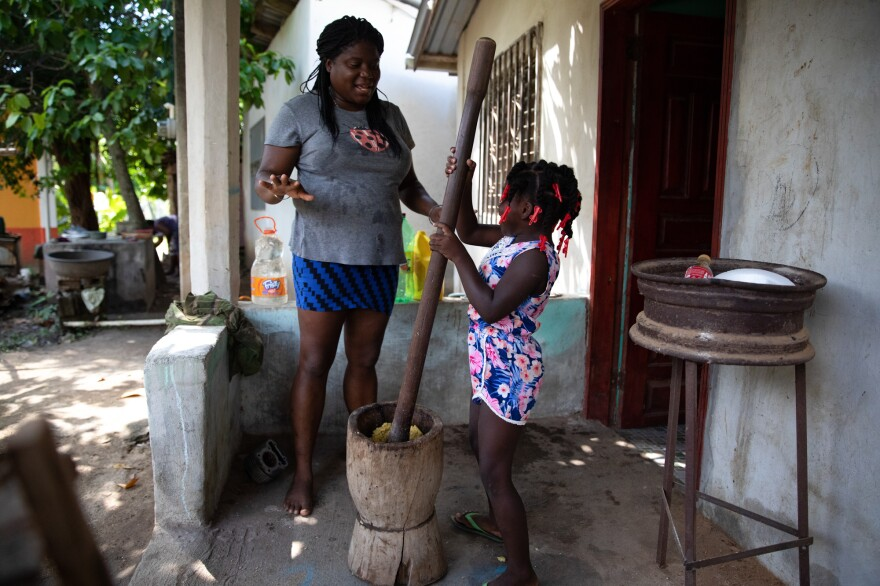 Ella's sister, Heidi, teaches her niece, 5-year-old Eleny, how to use the <em>hanaa</em>, the mortar used to mash plantains and traditional Garifuna staple grains. They're at their home in Rio Esteban.