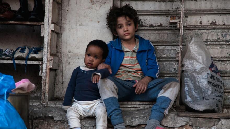 Yonis (Boluwatife Treasure Bankole), L, and Zain (Zain Al Rafeea), R, find a moment of quiet amid the chaos in <em>Capernaum.</em>