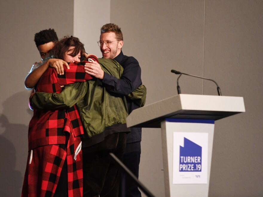 Tai Shani, Lawrence Abu Hamdan, Helen Cammock and Oscar Murillo go in for a group hug after learning their request to be considered joint winners was honored by Turner Prize judges.