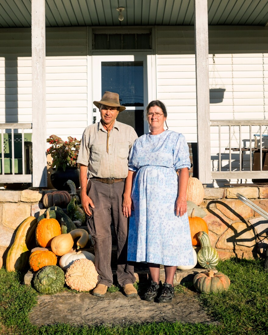 Charles Martin and his wife, Rosa, stand amidst some of their favorite gourds and squash from this year's harvest.