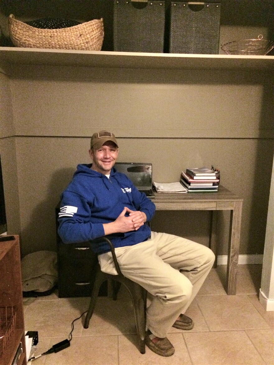 Veteran Travis Holt sits in the makeshift office he made in his spare bedroom.