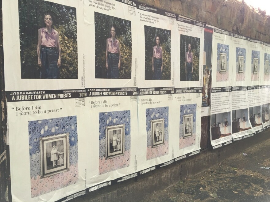 Posters touting the Women Priests Project along a wall.