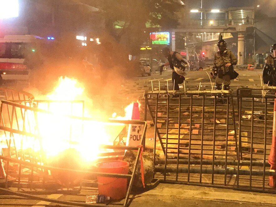 Hong Kong police inspect a barricade set ablaze by pro-democracy protesters who took to the streets on Sunday in demonstrations that at times turned violent.