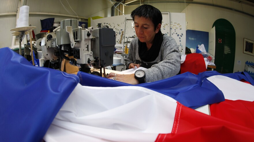 Michelle Houste sews a French flag at a factory near Lille, northern France on Thursday. There's been a surge in the demand for French flags since the Nov. 13 attacks in Paris.