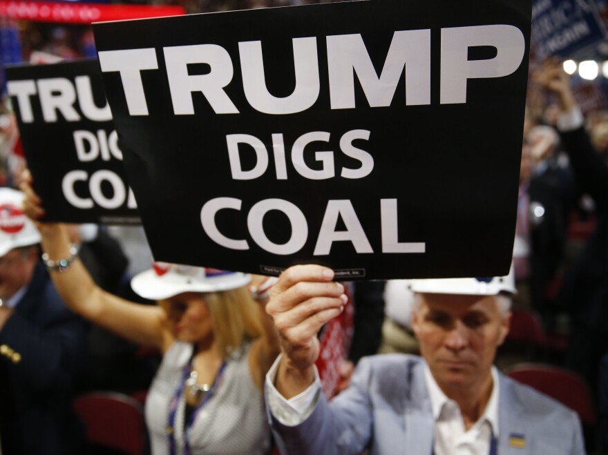"""A delegate holds a sign reading """"Trump Digs Coal"""" during the Republican National Convention in Cleveland in 2016."""