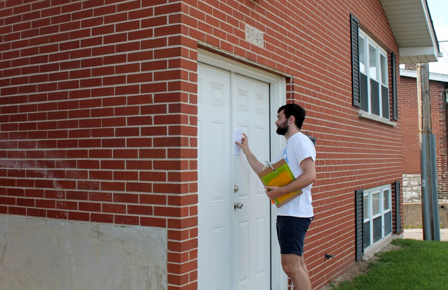 Gavin Schiffres slides a flyer between the doors of a home in the Dutchtown neighborhood June 8, 2017. He's trying to get the word out about a charter school he hopes to open in 2018.