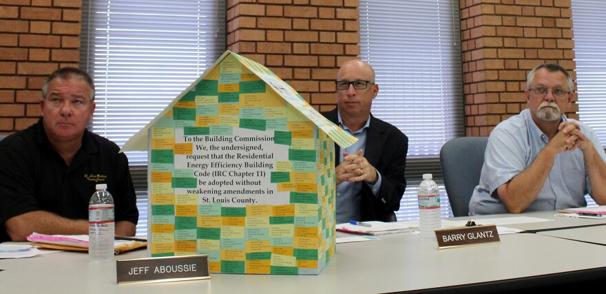 The St. Louis County Building Commission members (Jeff Aboussie, Barry Glantz and John Finder, right) listen to Sierra Club supporters on August 2015. The model house is covered with the names of 529 area residents who want stricter energy efficiency stan