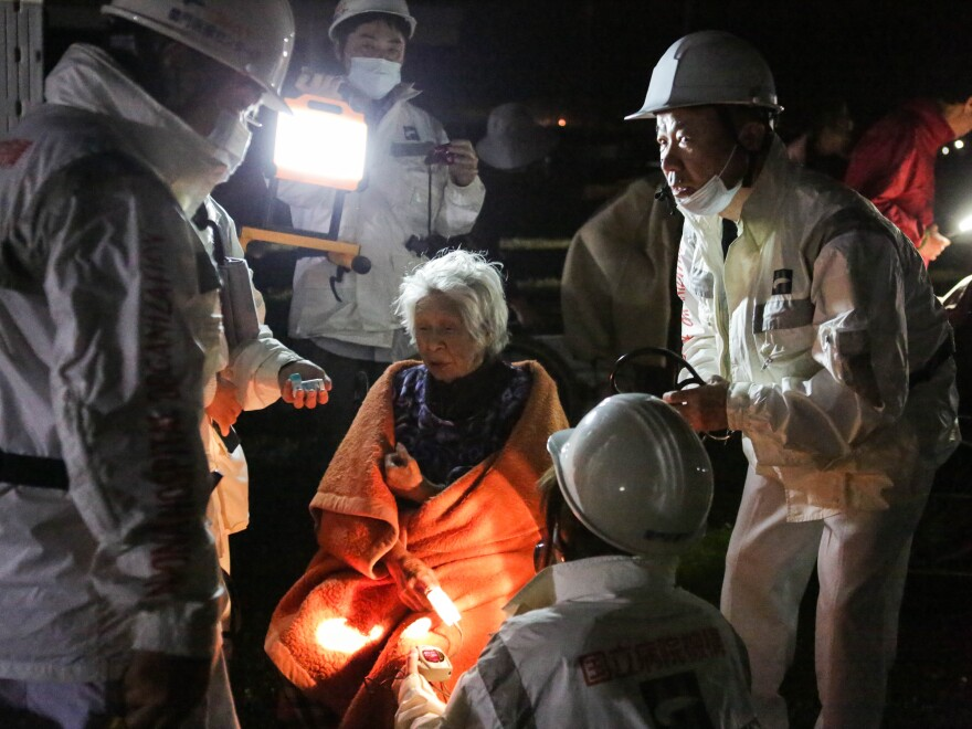 Rescue workers take care of an elderly woman after a 7.0 magnitude earthquake hit Kumamoto, Japan, early Saturday local time.