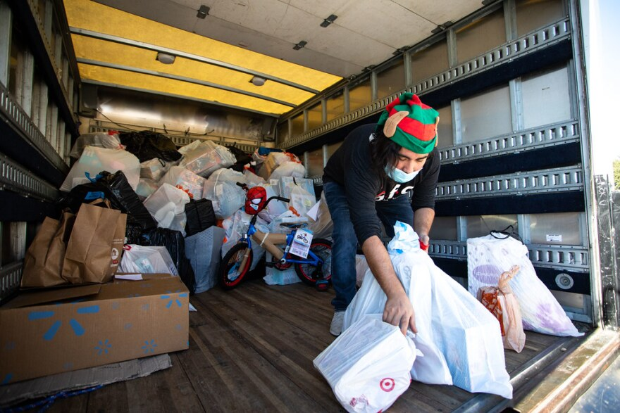 A person loads gifts into the back of a U-Haul truck.