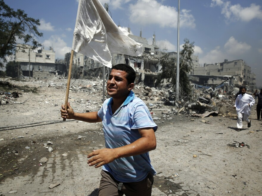 A Palestinian man runs with a white flag in the Shejaia neighborhood, which was heavily shelled by Israel during fighting in Gaza City on Sunday.