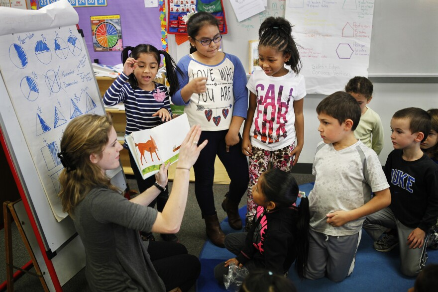 Teacher Elizabeth Carinder helps a group of her students present a book to their class.