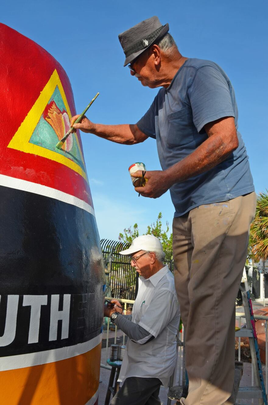 Artists Henry DelValle and Danny Acosta putting the finishing touches on the refurbished Southernmost Point Buoy. Mr. Acosta is the original artist to paint the iconic landmark.