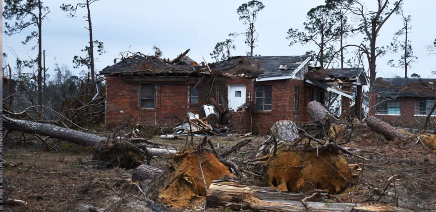 A badly damaged house with debris and trees strewn about the yard