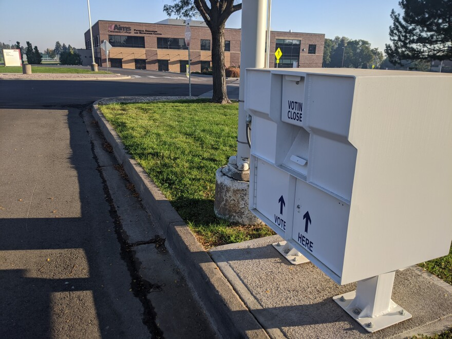 """A white box with """"Vote here"""" written on it secured to concrete."""